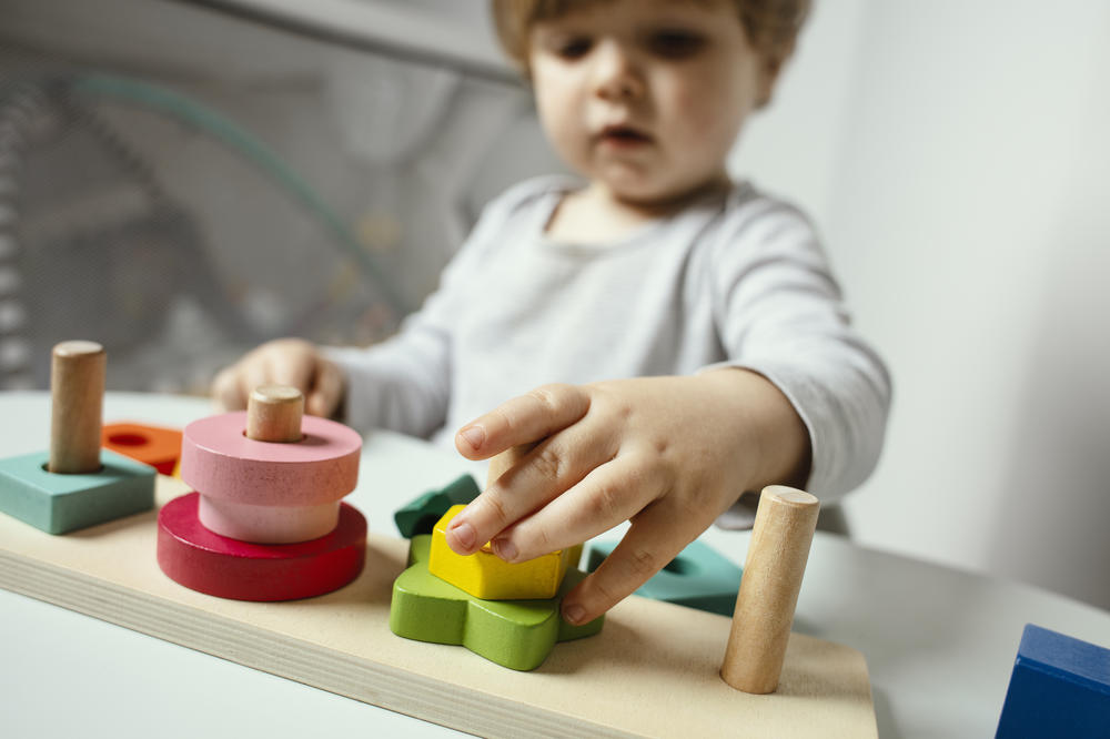 Beautiful toddler play with a wooden toys at home. Toddler play